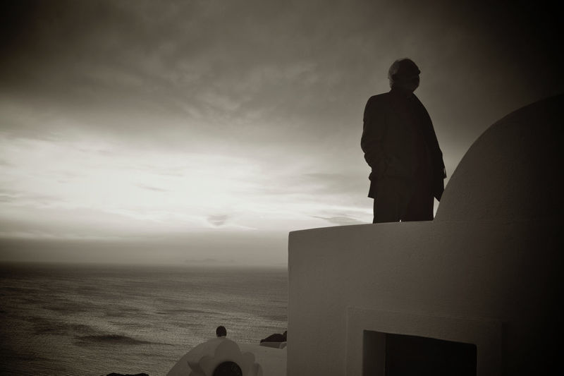 Rear view of silhouette man looking at sea against sky