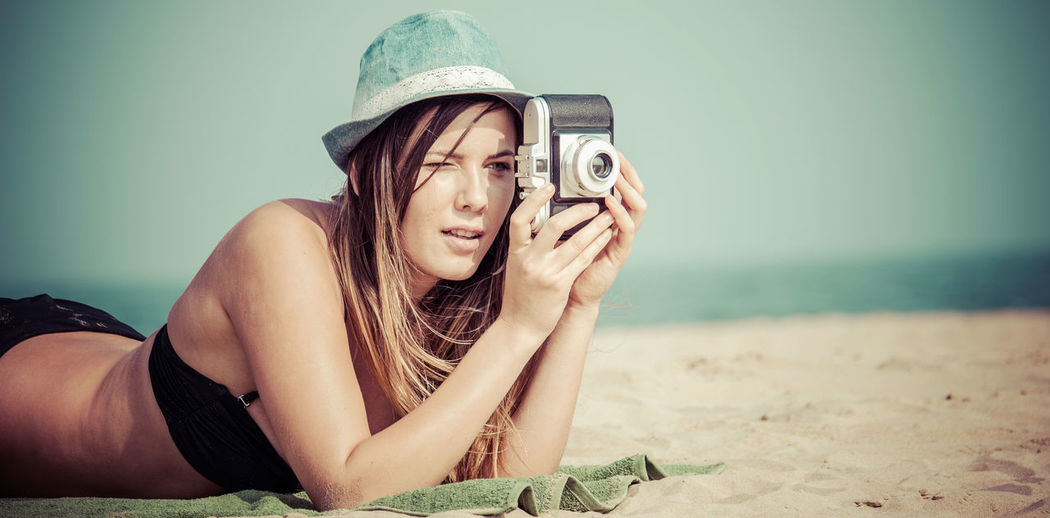 Young Woman Photographing With Camera While Lying On Sand At Beach