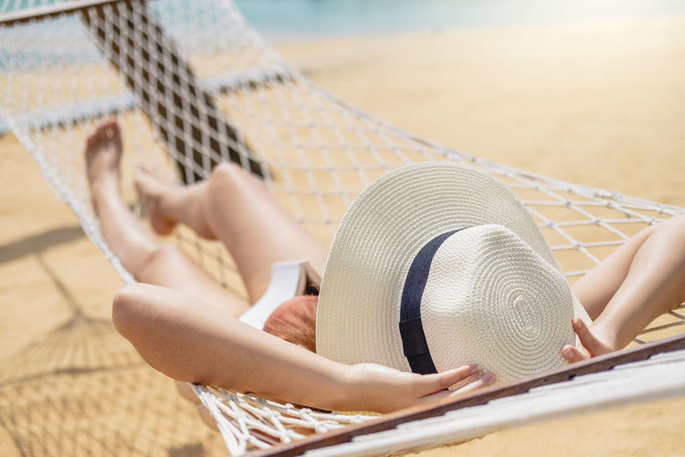 Low section of woman relaxing on hammock at beach