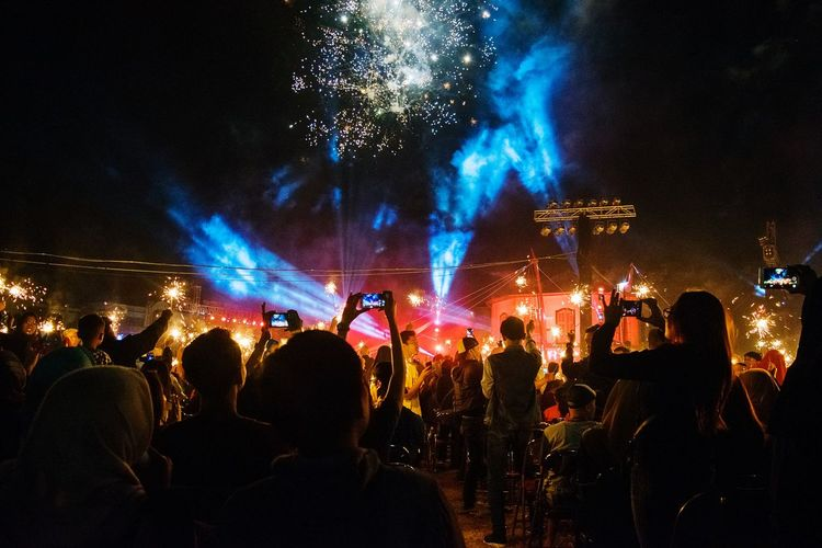 Rear view of people enjoying concert against firework display at night