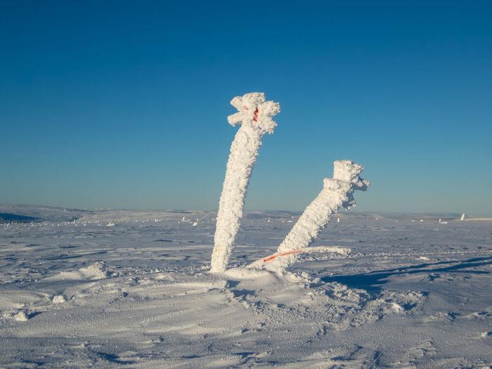 Snow on land against clear blue sky