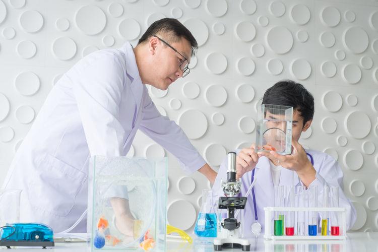 Scientists Performing Scientific Experiment At Laboratory