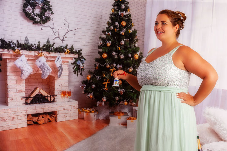 Woman standing by christmas tree at home