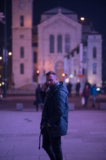 Portrait of man in warm clothing talking on mobile phone at night