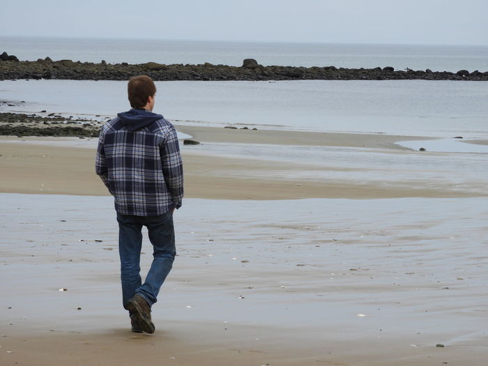 Rear View Of Man Walking On Shore At Beach