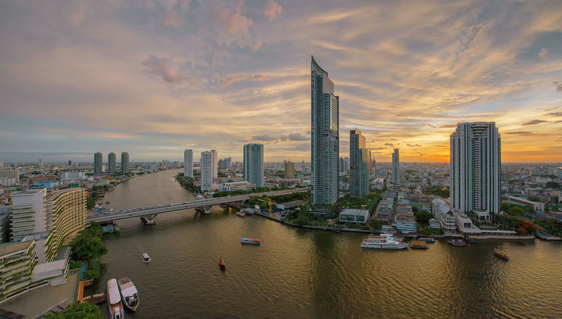 Chao Phraya River at sunset, Bangkok, Thailand Bangkok Chao Phaya River Cityscape Skyscrapers Thailand Architecture Building Exterior Buildings Built Structure City Cityscape Cloud - Sky Day Downtown District Modern No People Outdoors Sky Skyscraper Sunset Taksin Bridge Travel Destinations Urban Skyline Water