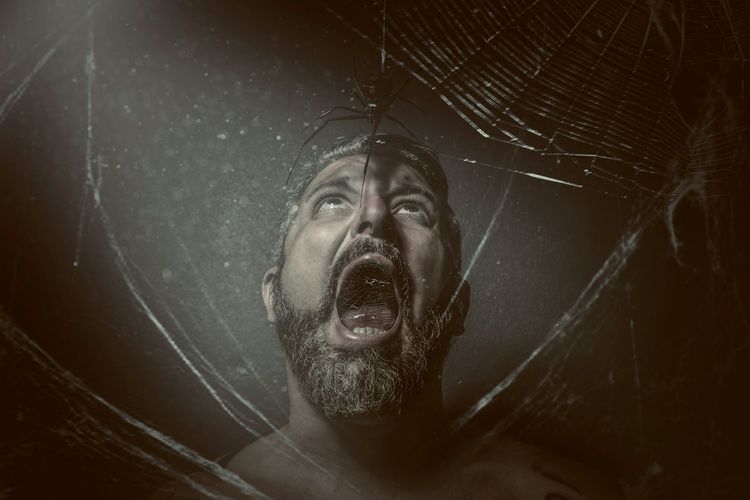 Man With Mouth Open Looking At Spider Against Black Background