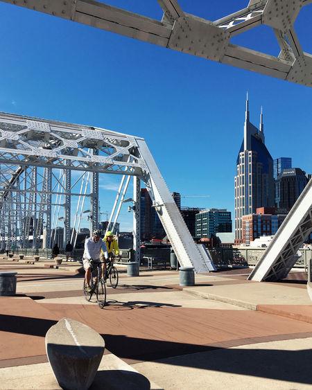 People on bridge against modern buildings in city