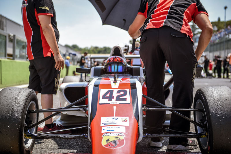 Formula 4 Abarth car on starting grid Abarth Adult Adults Only Competition Day Focus On Foreground Formula 4 Front View Low Section Men Motor Sport Occupation Outdoors People Professional Sport Real People Sport Sports Race Sports Team Sports Track Starting Grid Starting Line Teamwork Uniform