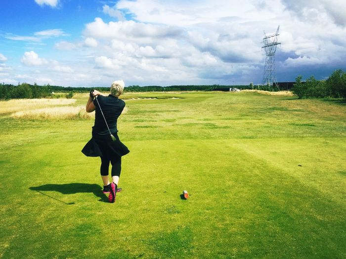 Full length rear view of playing golf against sky