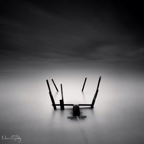 Silhouette chair against sky at dusk