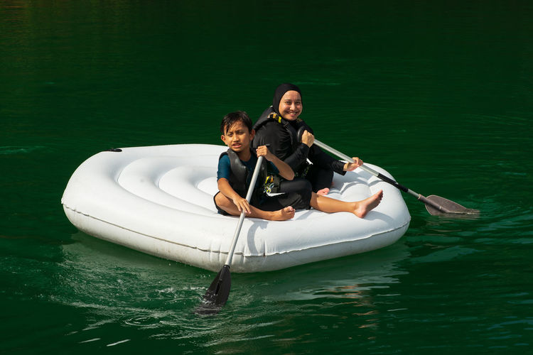 Portrait of mother and son sitting on boat in lake