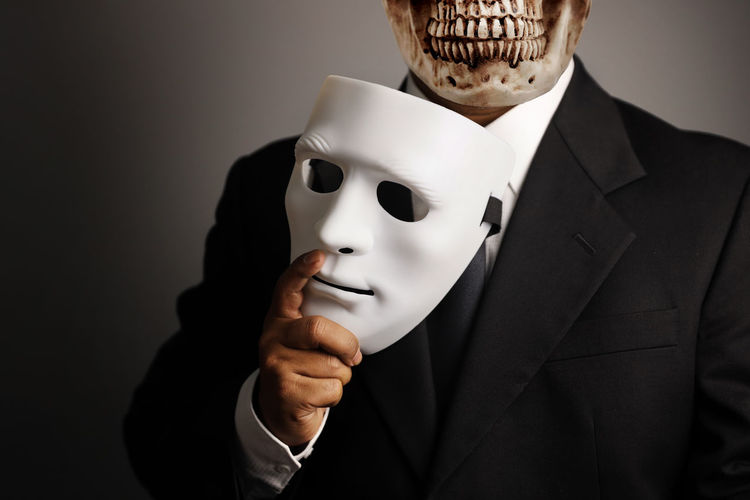 businessman or a man wearing black suit hiding skull face with white mask Betrayal Relationship Partner Background Mysterious Dark Secret Man Symbol Scary Security Identity Shadow Business Anonymous Horror Fear Law Crime Corruption Bribery Money Finance Pay Hand Businessman Illegal Financial Deal People Corrupt Cash Banknote Dollar Corruptibility Anti Hidden Adult HEAD Hiding Danger Criminal Threat Human Stranger Devil Violence Visibility Unknown