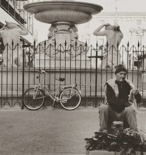 Streetphotography Monochrome Fountain Streetmarket One Man Only Fence Sculpture Urban Scene City Life Blackandwhitephotography City Bicycle Full Length