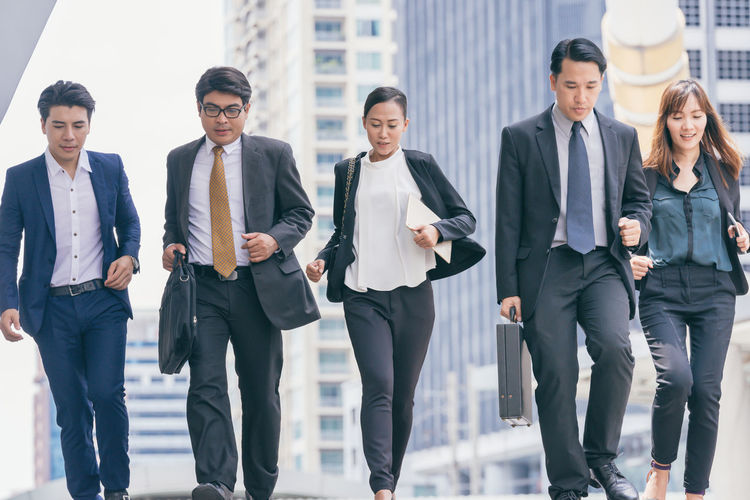 Business people running in city Asian  Business City Go Leader Running Rush Rush Hour Suit Teamwork Adult Architecture Building Business Person Businessman Businesswoman City Competition Leadership Manager Motion Portrait Suitcase Urban Walking