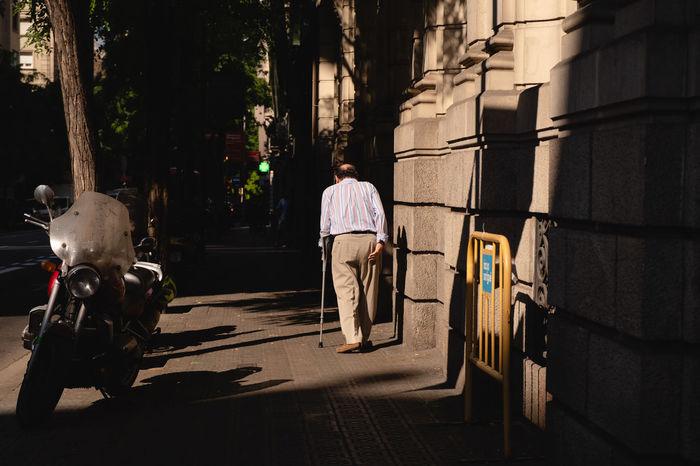 REAR VIEW OF MEN WALKING ON STREET AMIDST BUILDINGS
