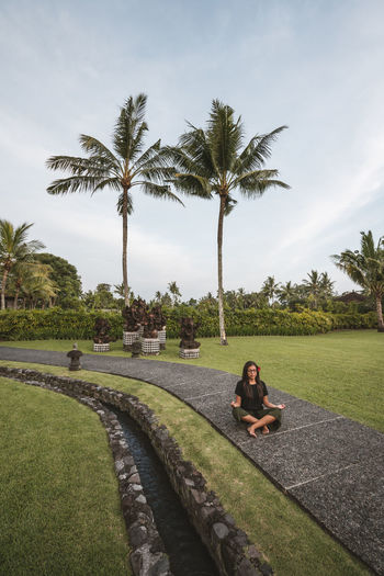 Woman sitting on palm trees