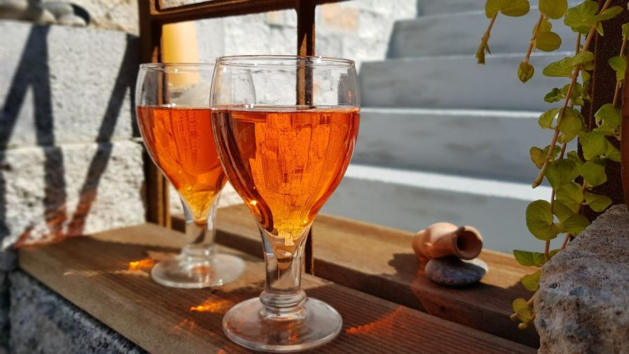 Close-up of two drinks of aperol  standing at the window shining in the sun