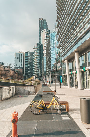 Bicycle on street by buildings against sky in city