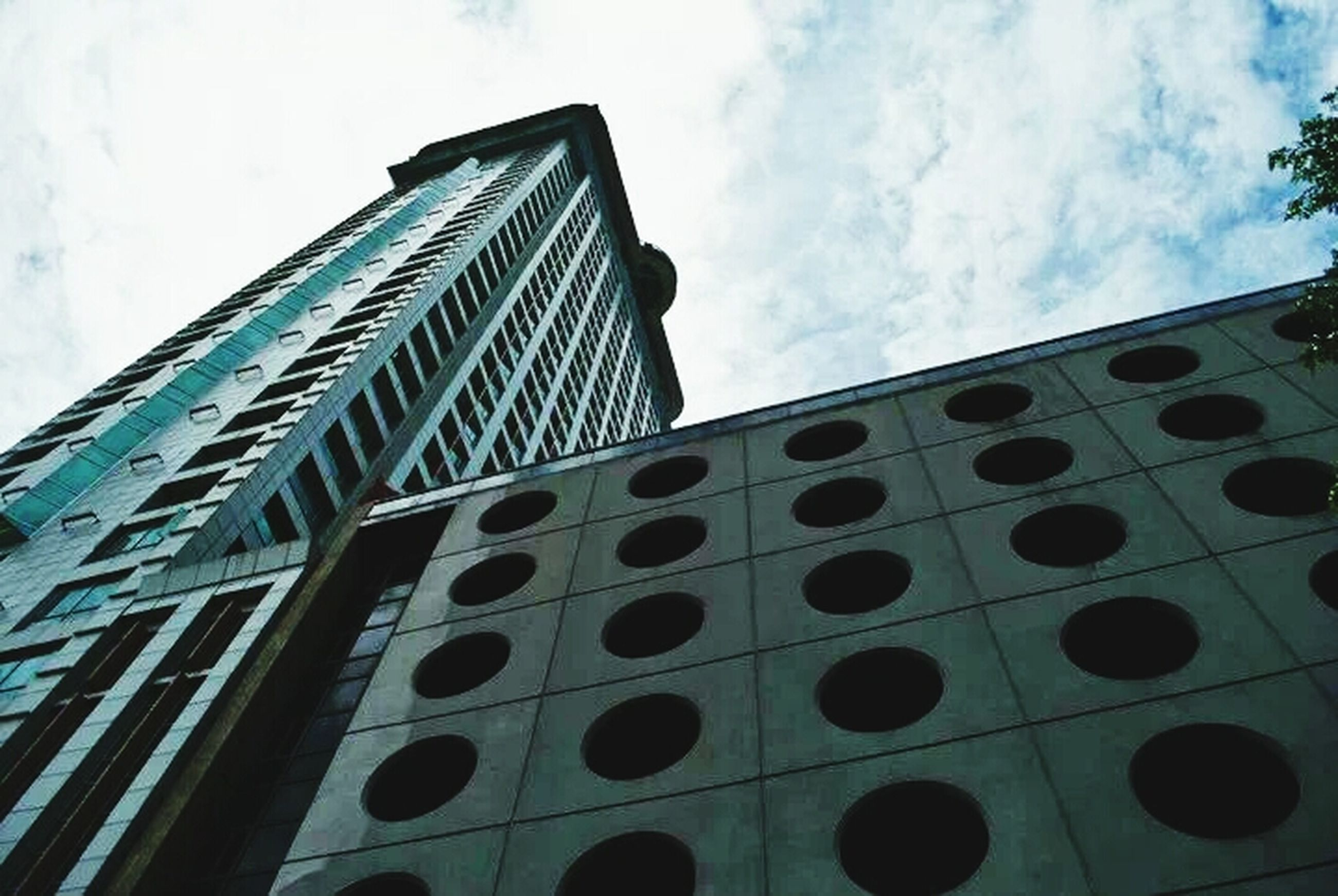 low angle view, architecture, built structure, building exterior, sky, building, modern, window, cloud - sky, glass - material, tall - high, tower, office building, pattern, city, day, no people, outdoors, cloud, architectural feature