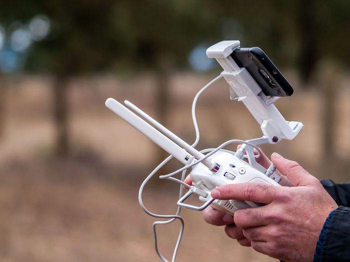Cropped hands of person using drone remote control and mobile phone