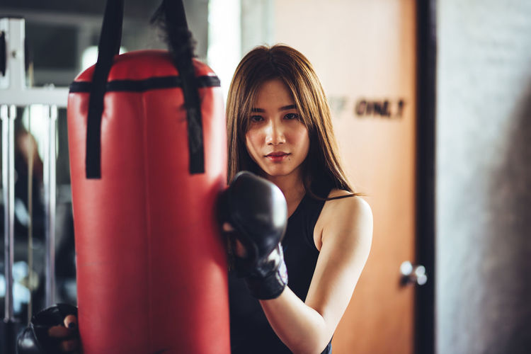Portrait Of Confident Young Woman Holding Punching Bag While Standing In Gym