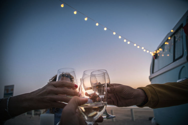 Cropped hands toasting wine outdoors during sunset