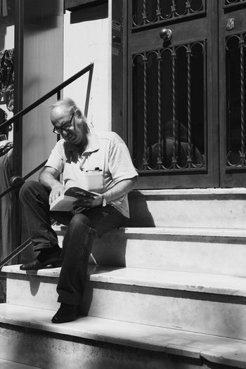 Reading The Street Photographer - 2018 EyeEm Awards Book Front View Monochrome One Person Reading A Book Reading Man Real People Sitting Staircase Street Photography Streetphoto_bw Streetphotography