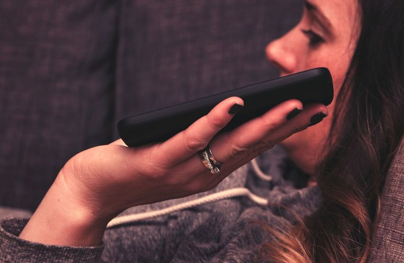 Woman holding mobile phone while lying down on sofa at home