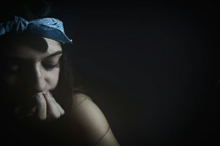 Close-up of young woman with bandana against black background