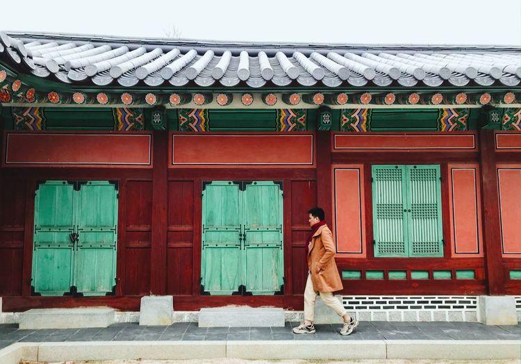Side view of man walking on footpath in city