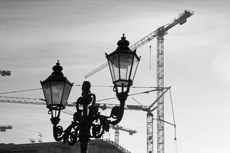 Low angle view of gas light with crane in background against sky