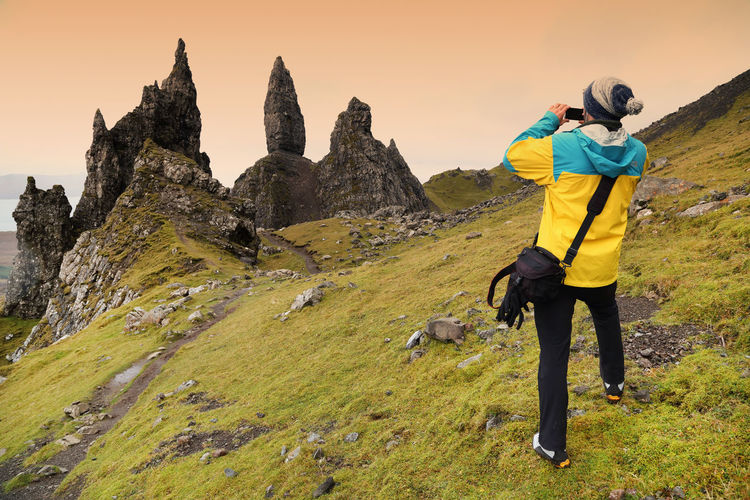 Rear view of man photographing old man of storr against sky during sunset