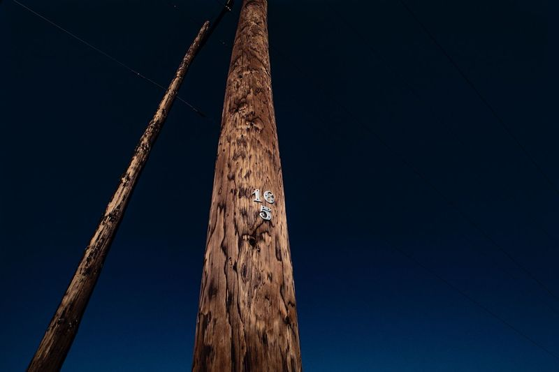 Low angle view of wooden post against clear sky