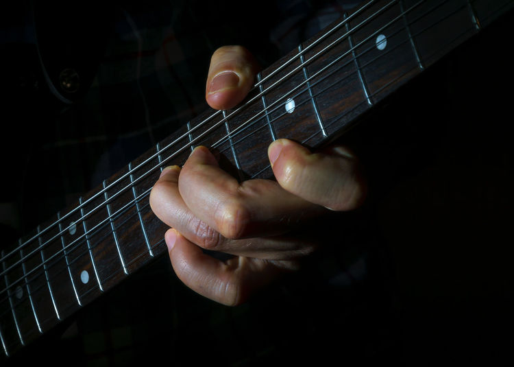 Close-up of hands playing guitar