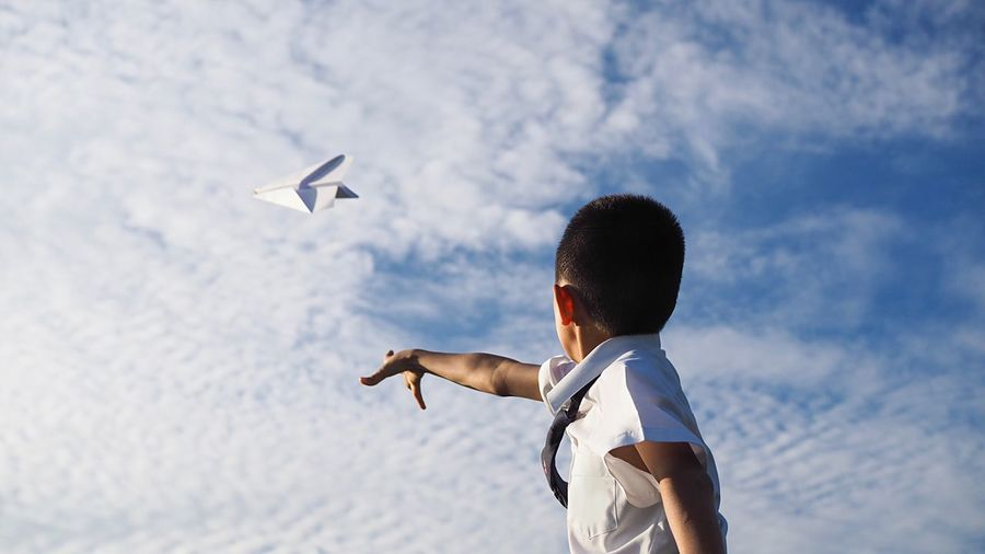 Side view of boy flying paper airplane against sky