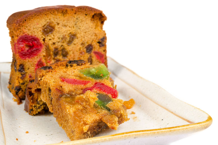 Delicious sliced fruit cake with mixed fruit and cherries on white plate isolated on white background Bakery Brown Color Candied Cherries Close-up Delicious Dessert Dish Food Freshness Fruitcake Healthy Food Isolated White Background Mixed No People Nutritious Food Pieces Raisins Sliced Snack Square Sugary Sultanas