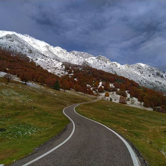 Road leading towards snowcapped mountain against sky