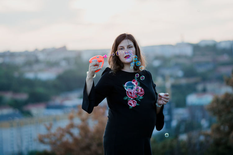 Portrait of woman holding bubble wand while standing outdoors