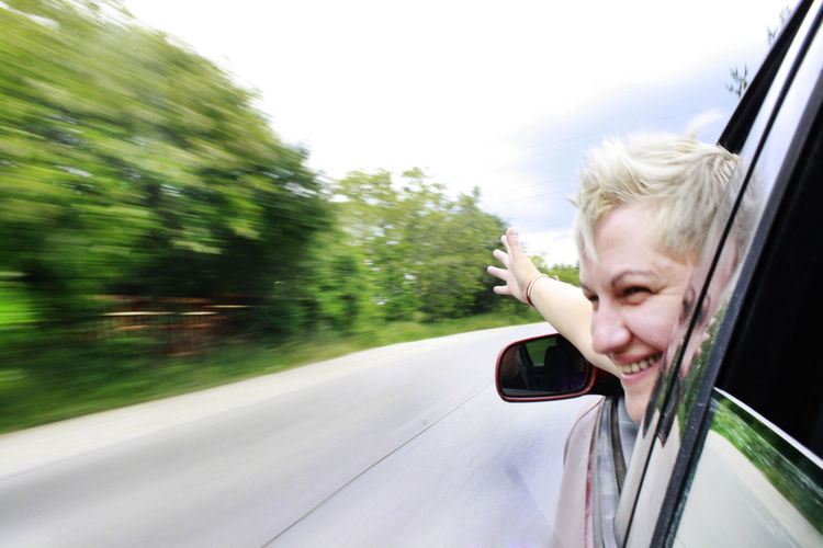 Close-Up Of Cheerful Woman Looking Through Car Window