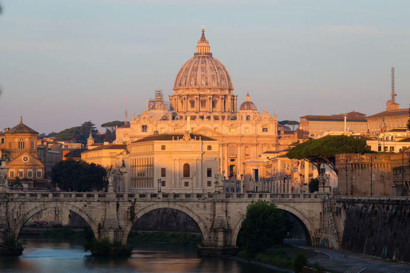 St Peter's Cathedral in Rome, Italy, and the Tiber River at sunrise Sky Built Structure Travel Destinations Tourism History Travel River No People Arch Outdoors Architecture Rome Vatican Tiber Tiber River Basilica Basilica Di San Pietro In Vaticano St Peters Basilica Pope Sunrise Blue Sky