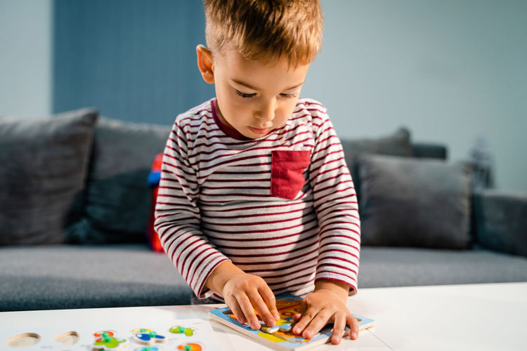 Cute boy playing with puzzle by table at home