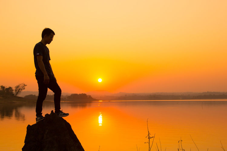 Full length of young man on rock by lake against sky during sunset