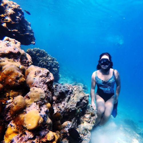Woman swimming by coral undersea