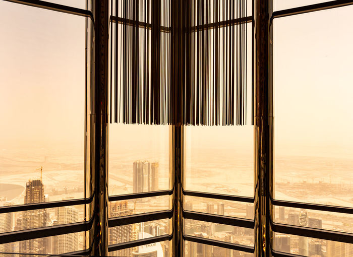 Close-up of railing against sky seen through glass window