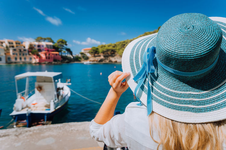 Woman Wearing Hat In City Against Sea