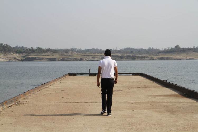 Rear view of man walking on pier against clear sky