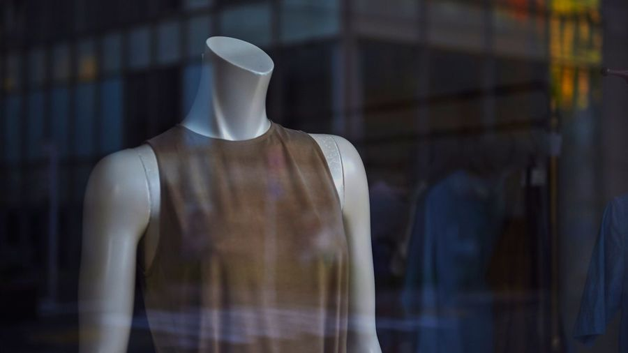Close-Up Of Female Mannequin In Glass Window Of Clothing Store