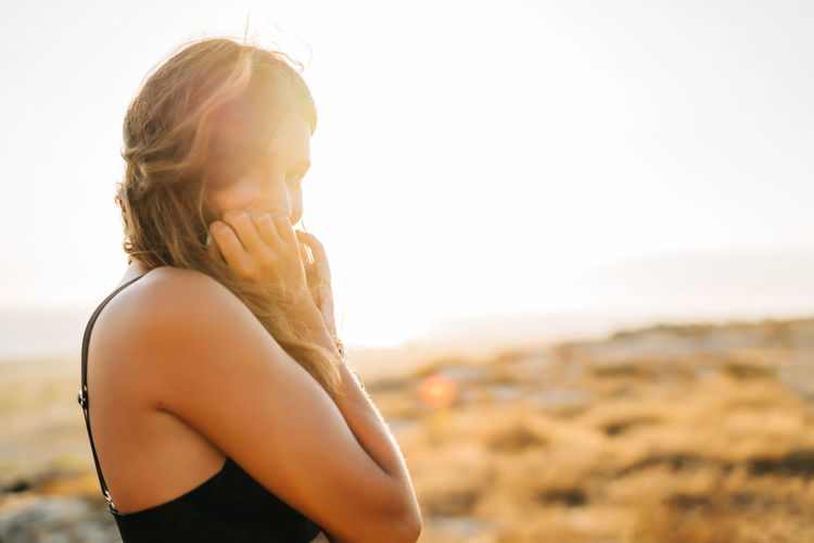 Portrait Of Young Woman Smiling While Standing At Beach During Sunset