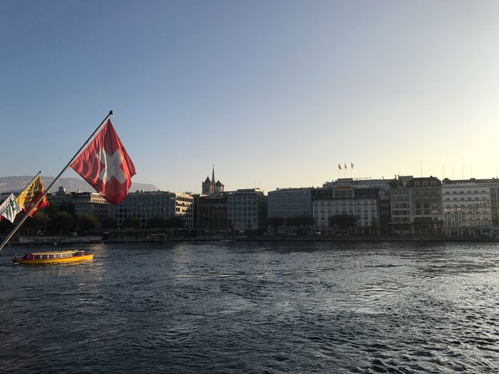 Swiss flag over lake by city against sky